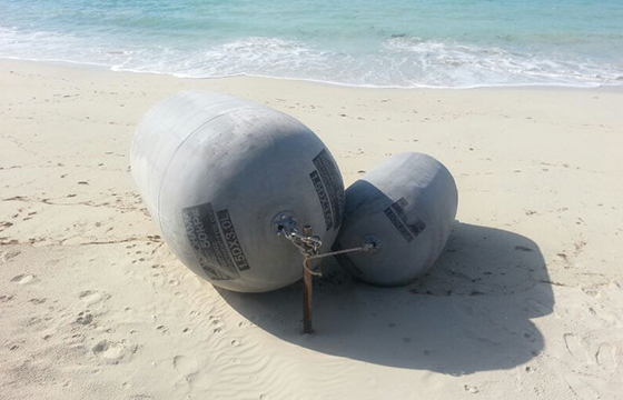 Naval lightweight grey fenders lying on a beach