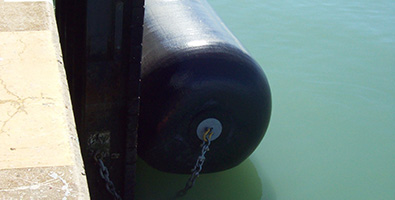 A floating foam fender attached to the quayside